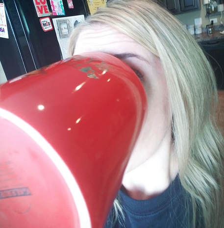 Female with blond hair drinking from jumbo coffee mug. Face is covered because mug is so big.